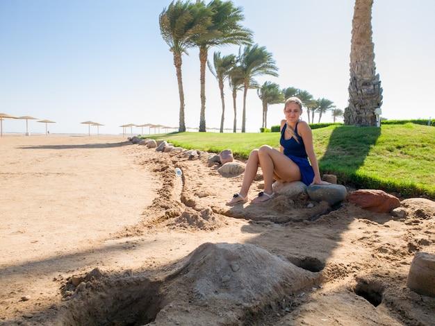 Mulher jovem e bonita com cabelo comprido sentada sob uma grande palmeira na praia do mar