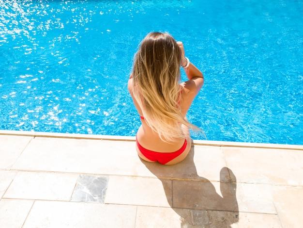 Mulher jovem e bonita com cabelo comprido, sentado à beira da piscina em uma villa luxuosa. mulher relaxando e se divertindo durante as férias de verão.