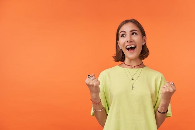 Mulher jovem e bonita com cabelo curto morena sorrindo. garota muito animada, olhe para o canto superior esquerdo no espaço de cópia na parede laranja. vestindo camiseta verde, colar, pulseiras e anéis