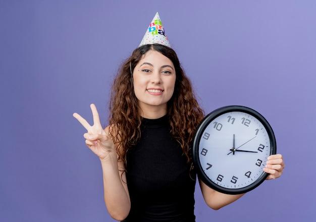 Mulher jovem e bonita com cabelo encaracolado com um boné de férias segurando um relógio de parede e sorrindo alegremente, mostrando o conceito de festa de aniversário com o sinal v em pé sobre a parede azul