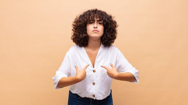 Mulher jovem e bonita com cabelo encaracolado e uma camisa branca