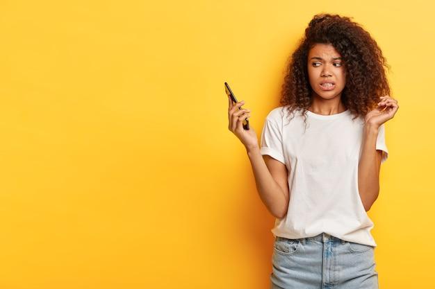 Mulher jovem e bonita com cabelo encaracolado posando com o telefone