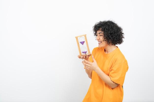 Mulher jovem e bonita com cabelo encaracolado, segurando uma ampulheta.