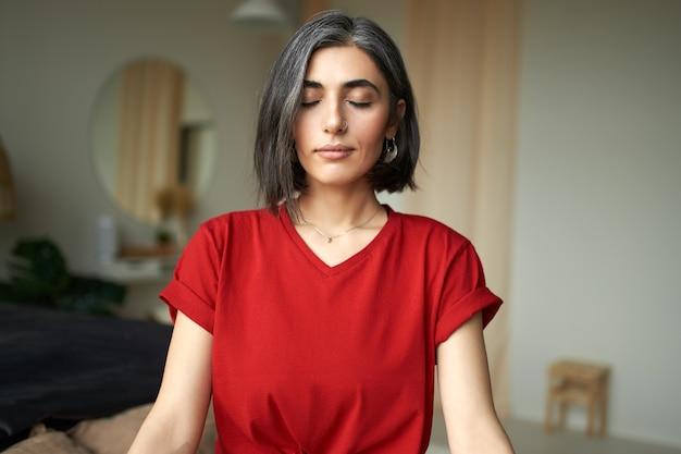Mulher jovem e bonita com cabelo grisalho e argola no nariz meditando dentro de casa, usando a técnica de respiração