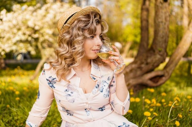 Mulher jovem e bonita com cabelo loiro com chapéu de palha bebe vinho e está sentada na manta no jardim durante um piquenique de verão