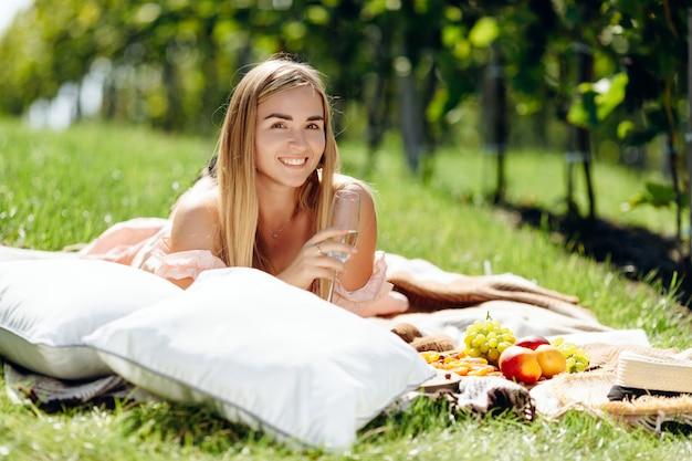 Mulher jovem e bonita com cabelo loiro, deitado sobre a manta no jardim uva, segurando um copo de vinho
