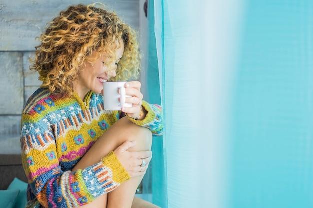 Mulher jovem e bonita com cabelo loiro encaracolado relaxa em casa bebendo chá - cores azuis e amarelas - conceito de pessoas felizes e solitárias curtindo o tempo - mulher branca bonita sorrindo e relaxando