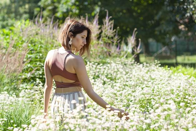 Mulher jovem e bonita com cabelo longo cacheado, vestida com vestido estilo boho, posando em um campo com flores.