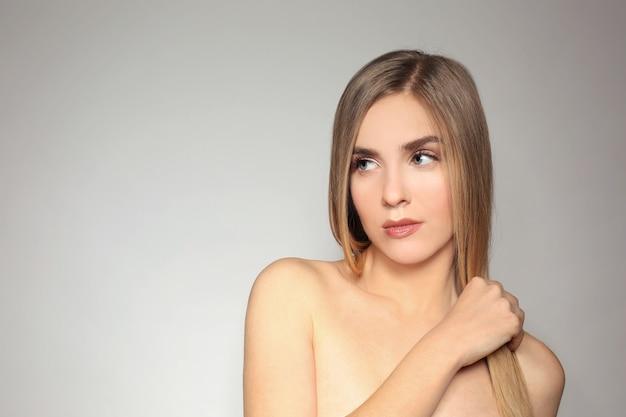 Mulher jovem e bonita com cabelo longo e reto sobre fundo claro