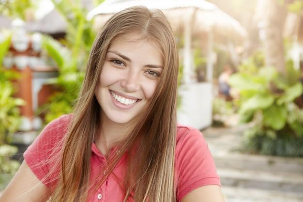 Mulher jovem e bonita com cabelo longo loiro, vestida de camisa pólo, olhando e sorrindo com uma expressão alegre e feliz, em pé ao ar livre contra plantas verdes