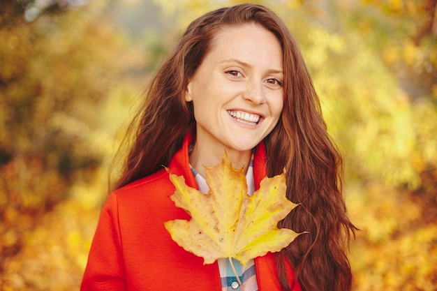 Mulher jovem e bonita com cabelo longo ondulado, cobrindo o rosto com uma folha