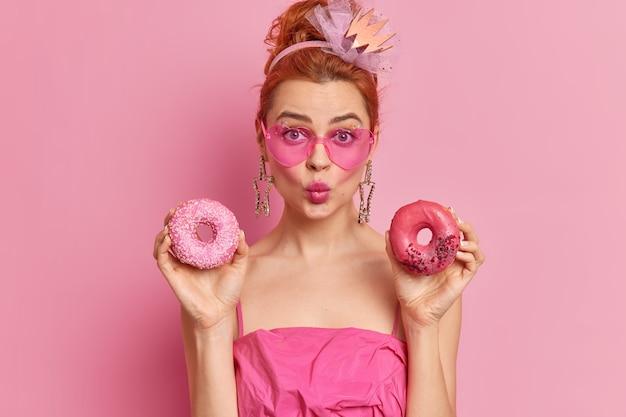 Mulher jovem e bonita com cabelo ruivo adora doces mantém os lábios dobrados segura dois donuts saborosos