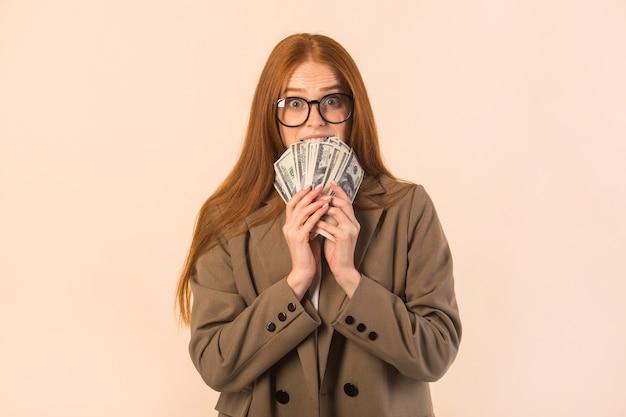 Mulher jovem e bonita com cabelo ruivo com uma jaqueta em um fundo bege