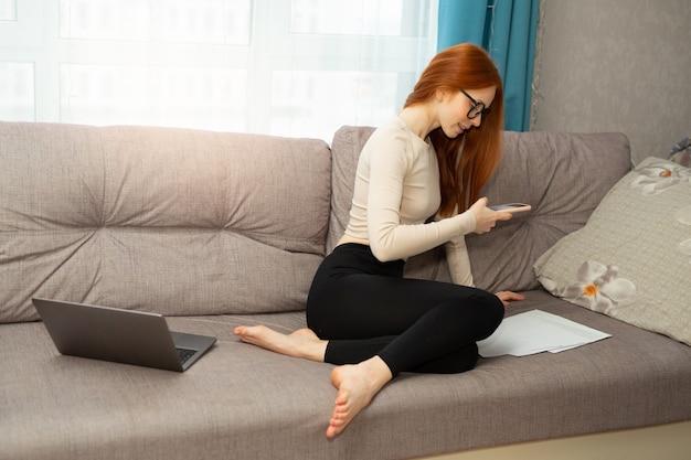 Mulher jovem e bonita com cabelo ruivo de óculos sentada no sofá com um laptop