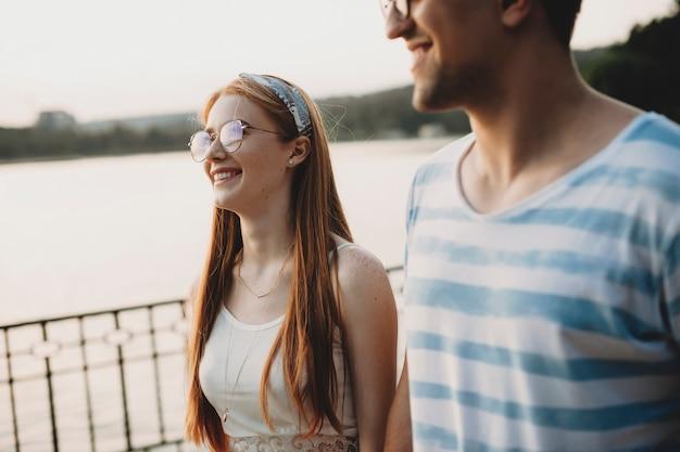 Mulher jovem e bonita com cabelo ruivo e sardas andando com seu amante no parque, sorrindo ao pôr do sol.