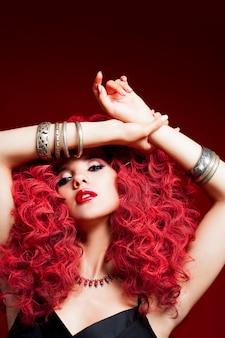Mulher jovem e bonita com cabelo vermelho. brilhante maquiagem e penteado