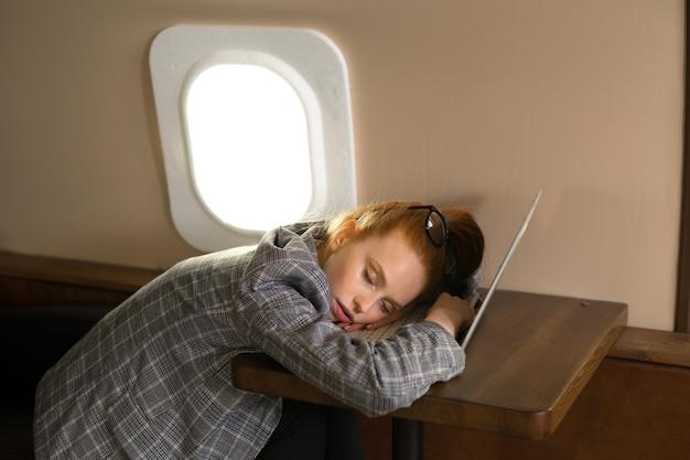 Mulher jovem e bonita com cabelo vermelho está voando em um avião da classe executiva e dormindo em um laptop