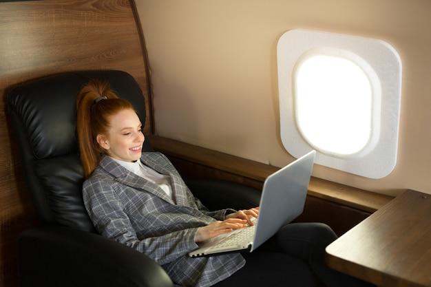 Mulher jovem e bonita com cabelo vermelho na cabine do avião com um laptop