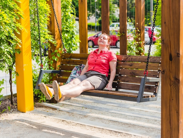 Mulher jovem e bonita com cabelo vermelho sentada em um banco em um parque da cidade, garota relaxada