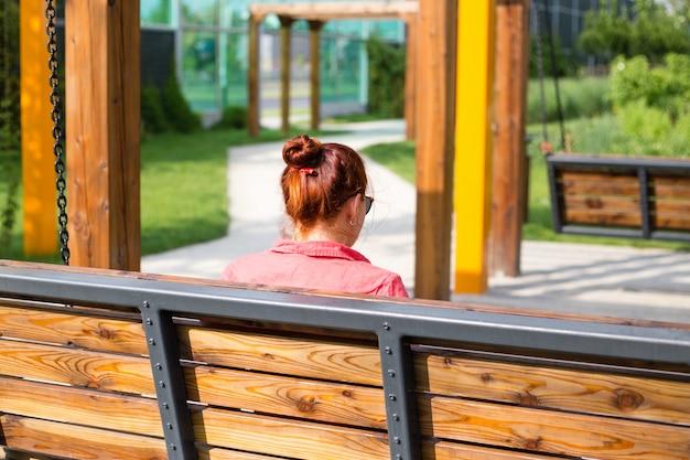 Mulher jovem e bonita com cabelo vermelho, sentada em um banco em um parque da cidade, mulher relaxada