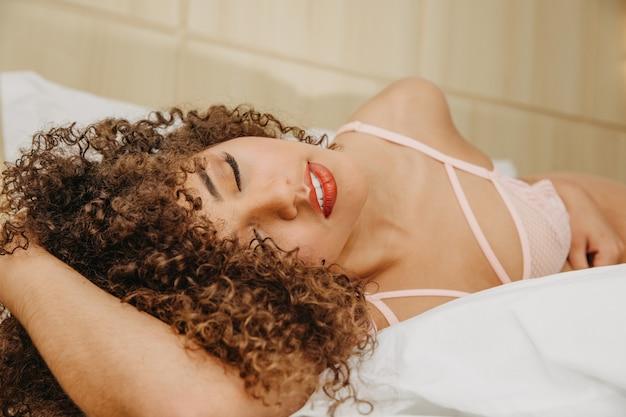 Mulher jovem e bonita com cabelos cacheados em lingerie sexy e sensual em uma cama posando