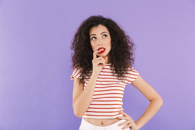 Mulher jovem e bonita com cabelos cacheados no desgaste do verão, olhando para cima e mordendo o dedo