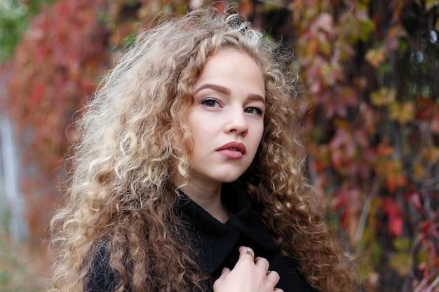 Mulher jovem e bonita com cabelos cacheados, olhos verdes. garota com roupas casuais, relaxando no parque com bom tempo de outono, coberta com folhas caídas.