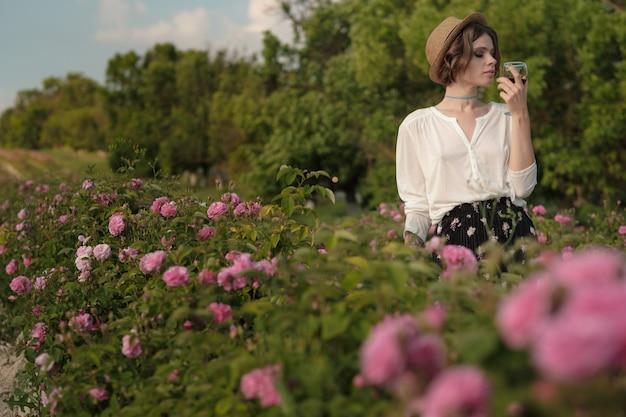 Mulher jovem e bonita com cabelos cacheados, posando perto de rosas em um jardim. o conceito de publicidade de perfume.