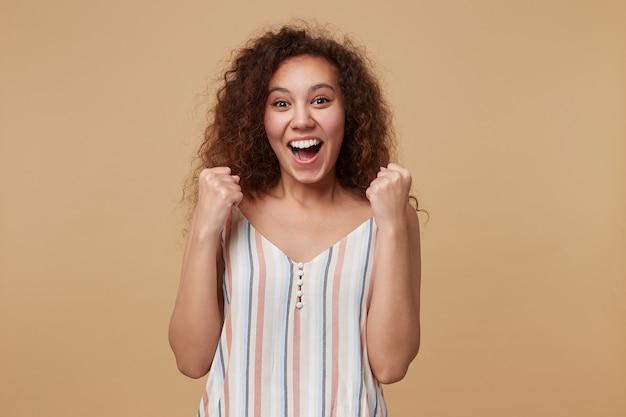 Mulher jovem e bonita com cabelos longos cacheados feliz com penteado casual levantando emocionalmente as mãos enquanto olha com alegria, isolado no bege