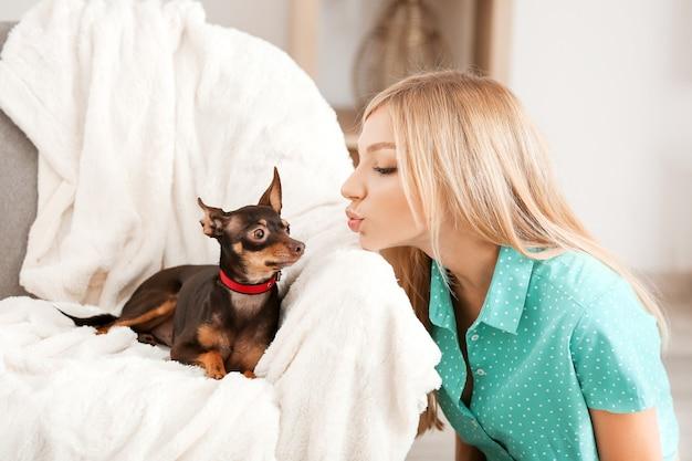 Mulher jovem e bonita com cachorro terrier de brinquedo fofo em casa