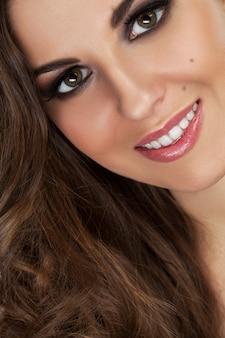 Mulher jovem e bonita com cachos e maquiagem