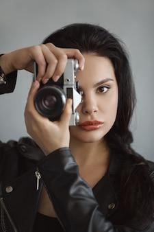 Mulher jovem e bonita com câmera fotográfica dentro de casa. retrato de close-up de hipster elegante jovem
