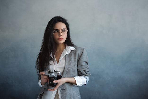 Mulher jovem e bonita com câmera fotográfica dentro de casa. retrato de jovem fotógrafa na moda