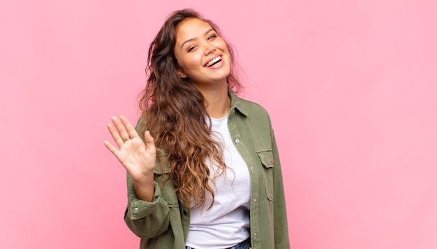 Mulher jovem e bonita com camisa aberta jeans verde posando na parede rosa