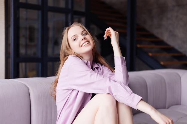 Mulher jovem e bonita com camisa roxa no sofá, sorrindo sozinha