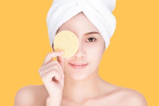 Mulher jovem e bonita com cara de limpeza por esponja, isolada com traçado de recorte