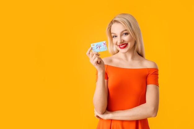 Mulher jovem e bonita com cartão-presente na superfície colorida