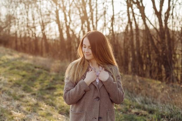 Mulher jovem e bonita com casaco de lã na floresta ao pôr do sol