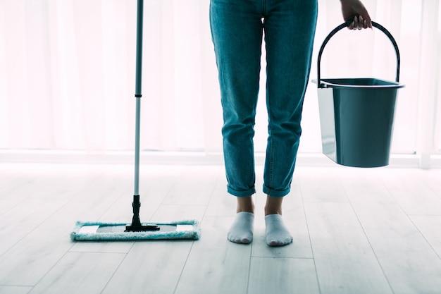 Mulher jovem e bonita com cesto e esfregão limpando o chão em casa