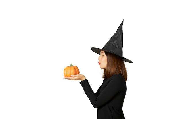 Mulher jovem e bonita com chapéu de bruxa segurando uma lanterna de abóbora de halloween
