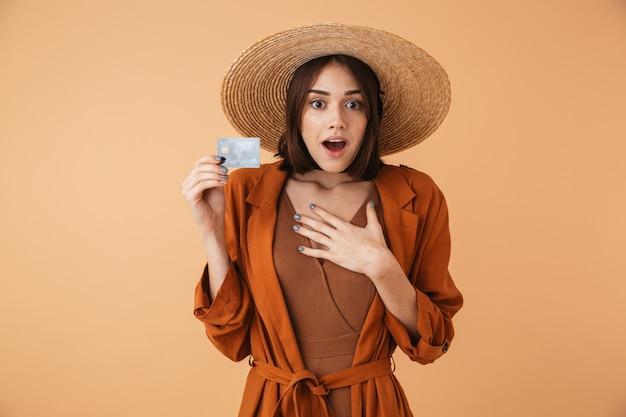Mulher jovem e bonita com chapéu de palha e roupa de verão em pé, isolada sobre uma parede bege, mostrando um cartão de crédito de plástico