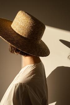 Mulher jovem e bonita com chapéu de palha e vestido branco vestido de verão contra a parede. silhueta na luz solar. sombras na parede