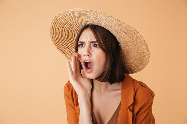 Mulher jovem e bonita com chapéu de palha isolada sobre uma parede bege, gritando