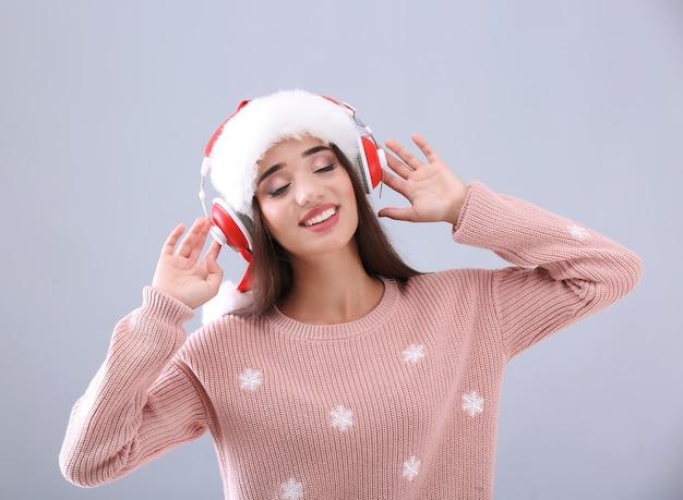 Mulher jovem e bonita com chapéu de papai noel ouvindo música de natal em cinza
