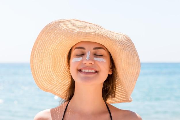 Mulher jovem e bonita com chapéu está aplicando protetor solar sob os olhos e no nariz como um índio. conceito de proteção solar.