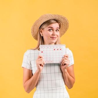 Mulher jovem e bonita com chapéu mostrando o calendário de ovulação