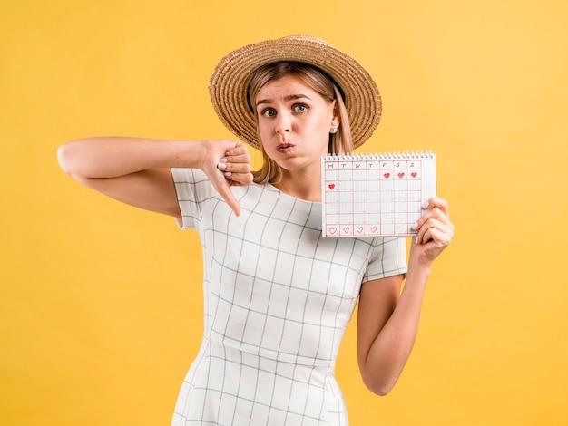 Mulher jovem e bonita com chapéu polegares para baixo