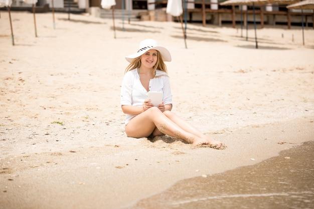 Mulher jovem e bonita com chapéu, sentada na praia e usando tablet digital