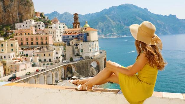 Mulher jovem e bonita com chapéu sentado na parede olhando para o stunni