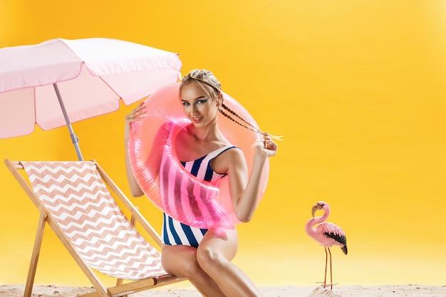 Mulher jovem e bonita com círculo de natação lazer e moda elegante